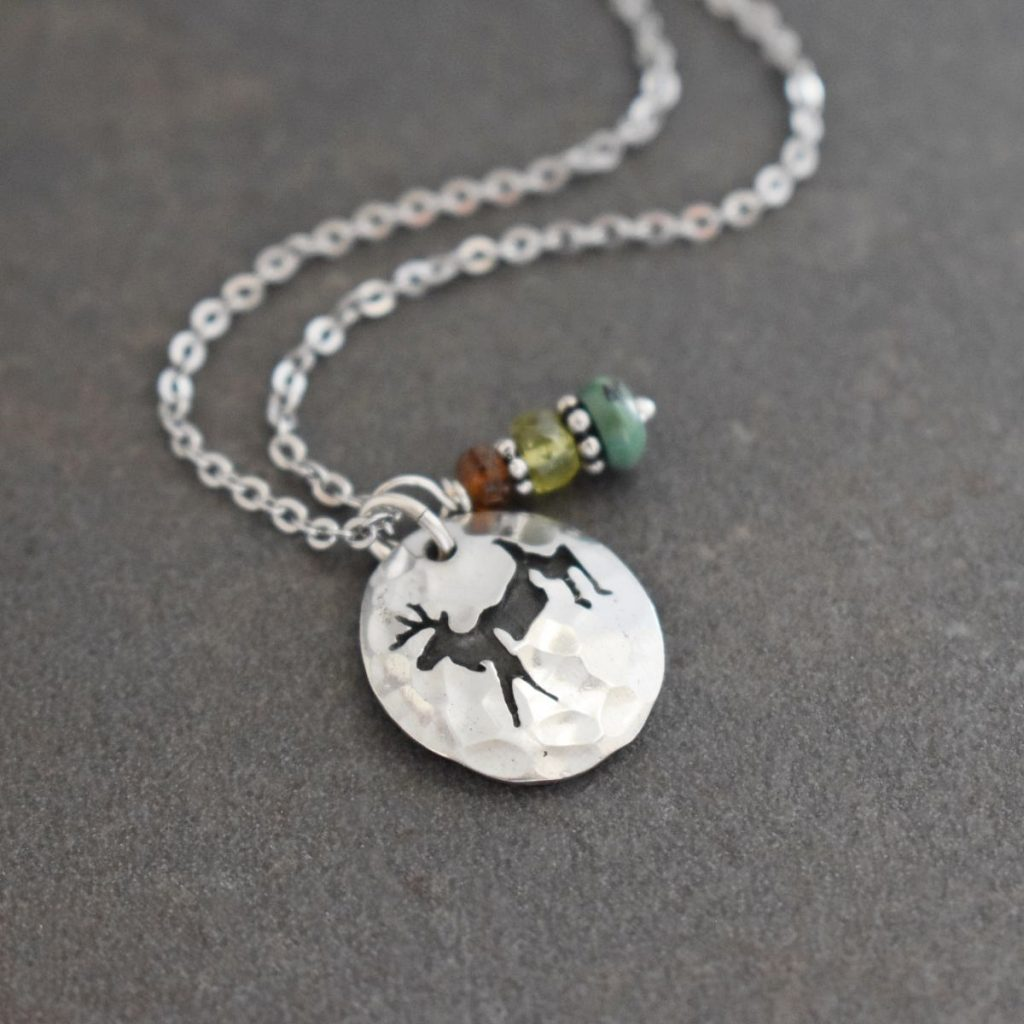 silver oval pendant with jumping deer with brown and green gemstones