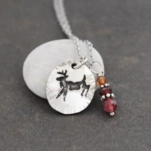 silver deer pendant with copper and pink gemstones
