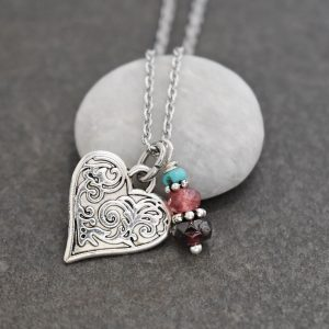 silver heart with floral designs pendant and pink and maroon gemstones